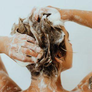 femme brune fesant un shampoing